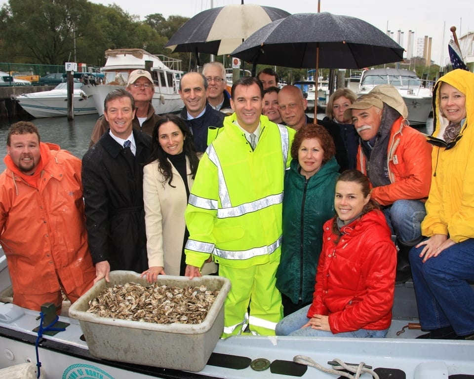 Image of group of locals around shellfish from the harbor.